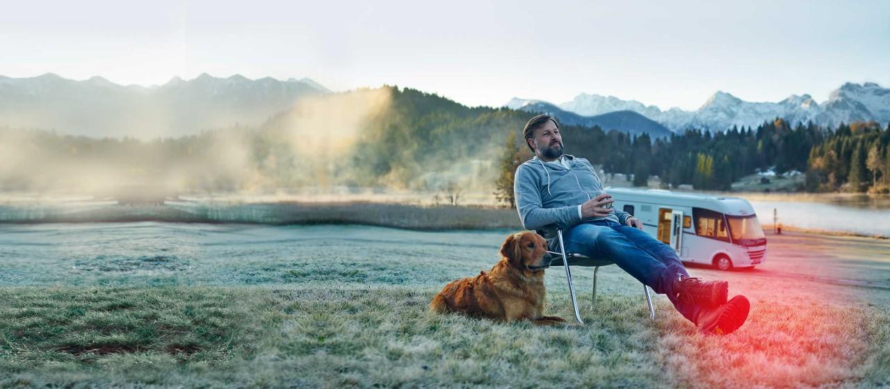 Mann mit Hund vor Wohnmobil
